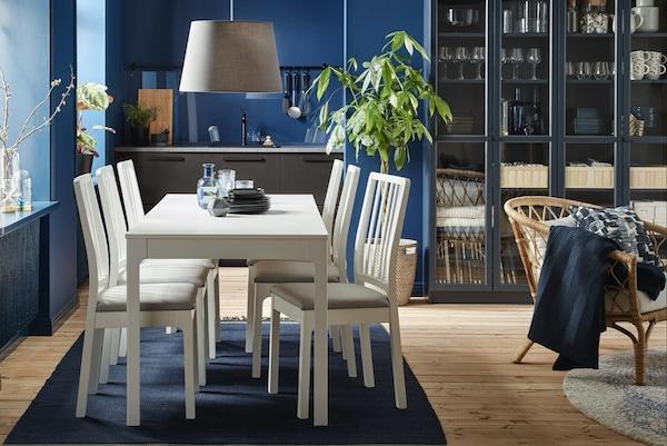 Ein gemütlicher Essbereich mit einem weißen Tisch auf einem blauen Teppich.