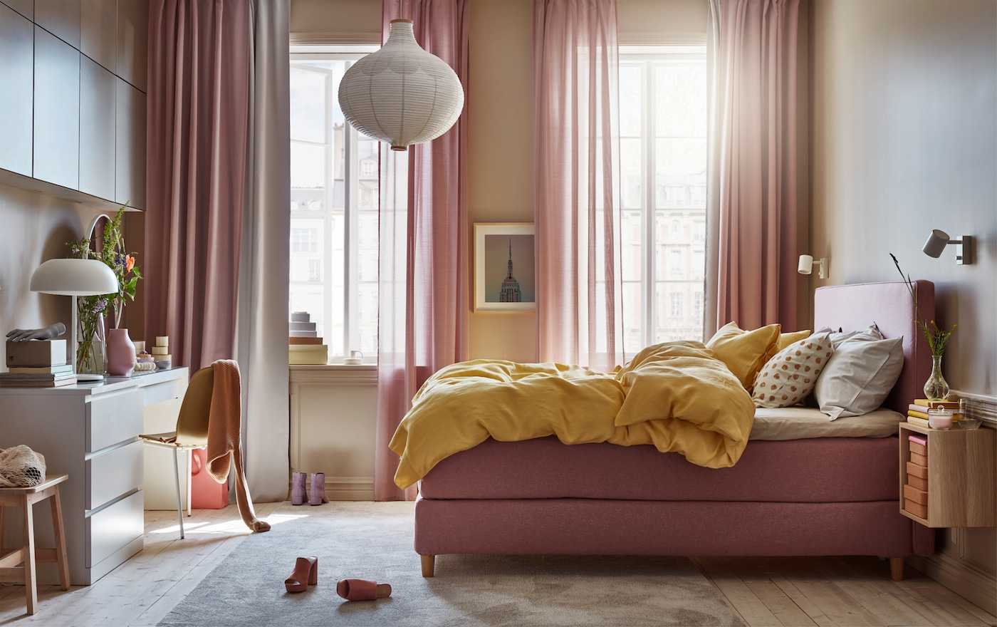 Ein gemütliches Schlafzimmer in braun-rosa mit gelber Bettwäsche, weißen Leuchten, Frisiertisch und braunem Regalelement.