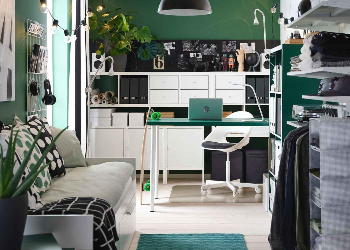 Ein gemütliches Studierzimmer mit weißer Schlafcouch, weißem Stuhl, Schreibtisch, grünem Regal und schwarzer Lampe.
