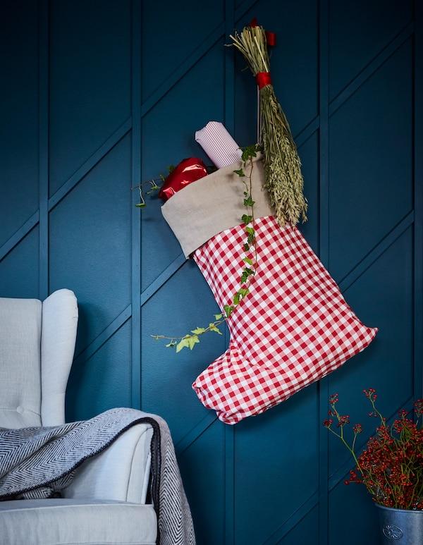Ein Geschenkbeutel zu Weihnachten in Form eines Weihnachtsstrumpfes hängt an einer blauen Wand.