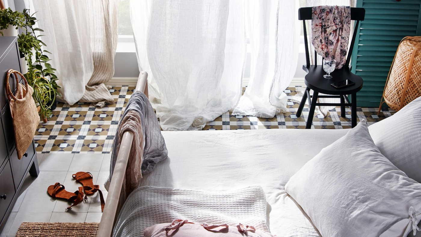 Ein GJÖRA Bettgestell und ein NORRARYD Stuhl stehen auf einem gefliesten Boden vor einer Flügeltür mit weißen und beigefarbenen Gardinen.