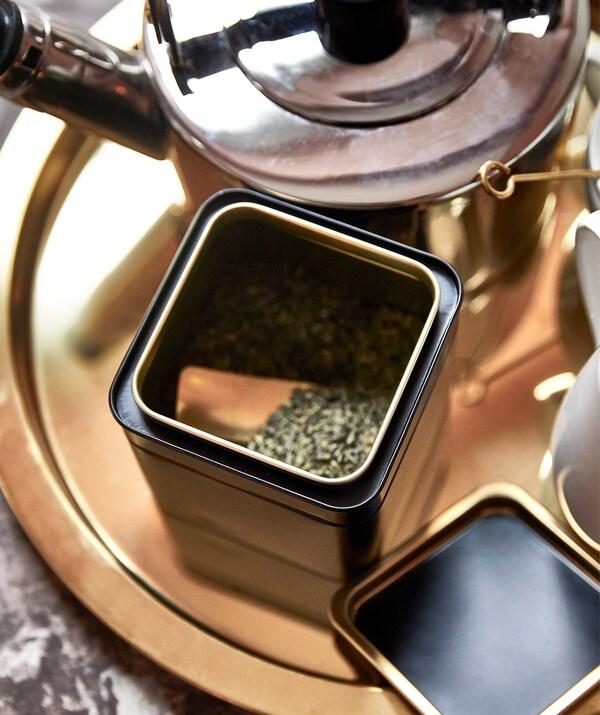 Ein goldfarbenes, rundes Tablett, u. a. mit einer BLOMNING Kaffee-/Teedose und zwei Tassen