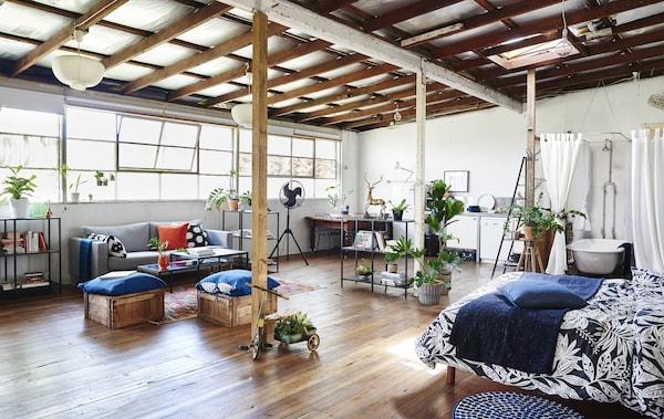 Ein großer, offen gestalteter Wohnraum mit Bett, Badezimmer und Sofabereich