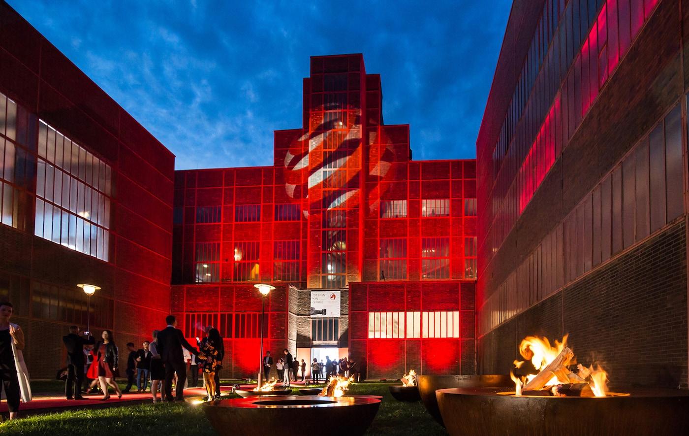 Ein großes Gebäude, das mit roten Scheinwerfern und dem Logo der Red Dot Awards angestrahlt wird.