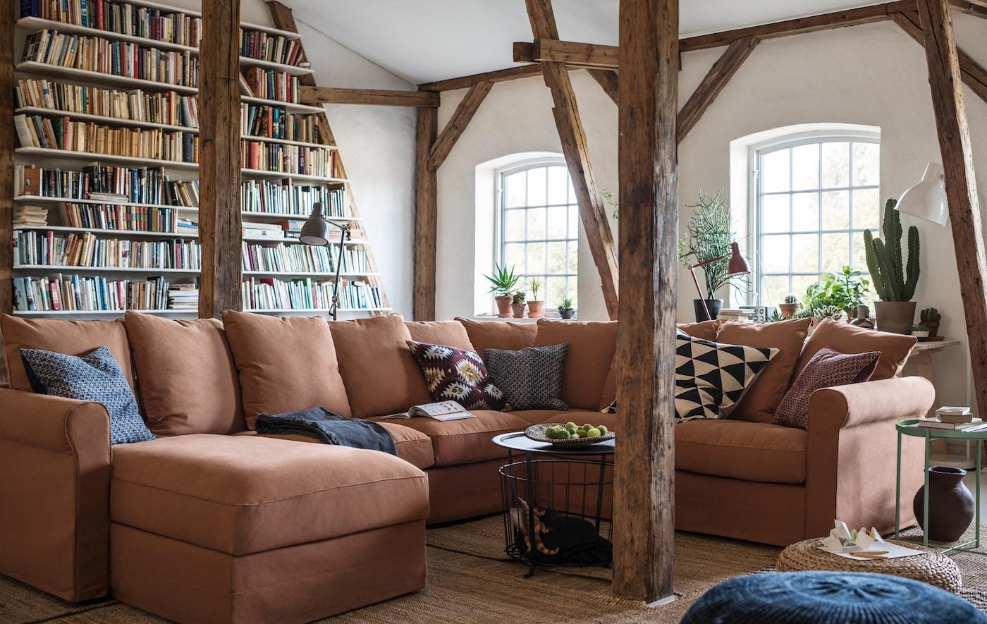 Ein grosses, U-förmiges Sofa in einem Raum mit freiliegenden Balken.
