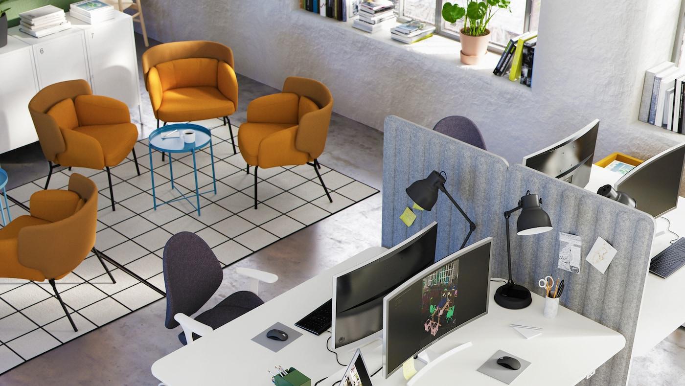 Ein Großraumbüro mit einem Sitzbereich, in dem Sessel um Couchtische stehen, und einem Arbeitsbereich, der durch Raumteiler unterteilt ist.