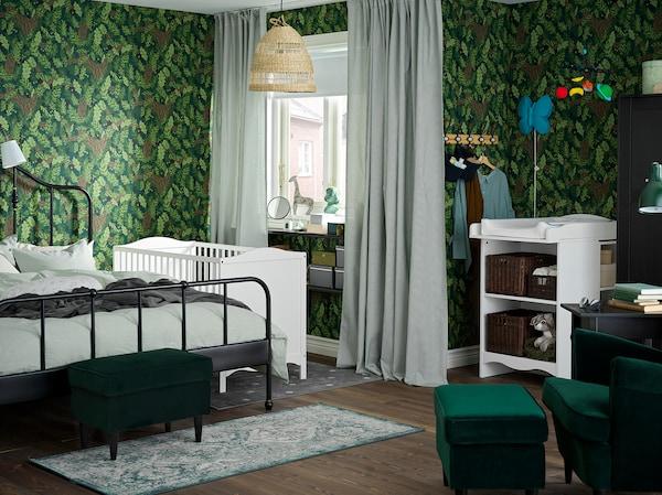 Ein grün gehaltenes Schlaf-/Kinderzimmer mit Wickeltisch und Babybett in Weiß und einem schwarzen Bettgestell für die Eltern.