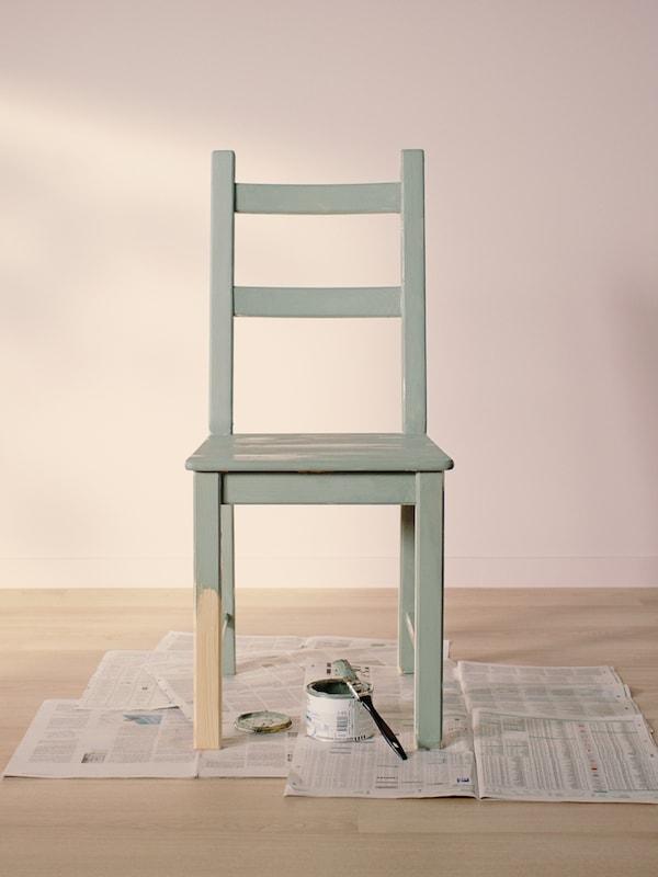 Ein grün gestrichener IVAR Stuhl steht in einem leeren Zimmer mit einem hellen Holzboden und Wänden in Hellrosa auf alten Zeitungen.