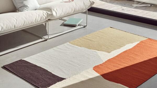 Ein handgefertigter bunter Teppich liegt auf einem grauen Boden in einem modernen Wohnzimmer.