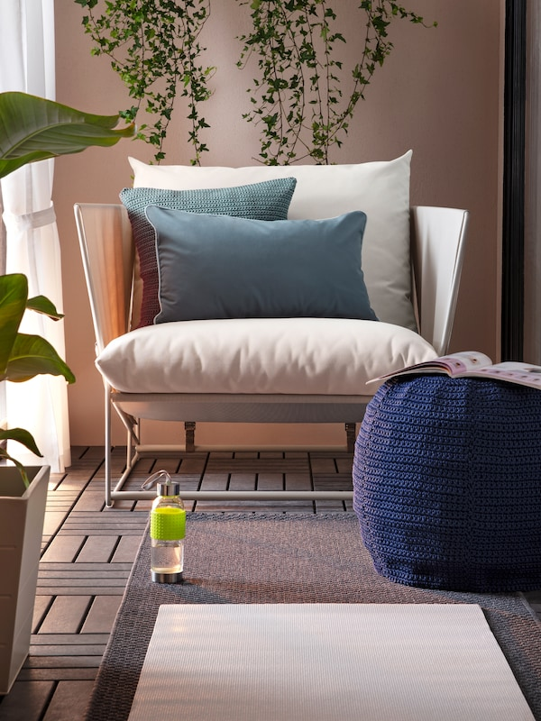 Ein HAVSTEN Sessel und graue Kissen auf einem Bodenrost, auf dem ein Teppich liegt.