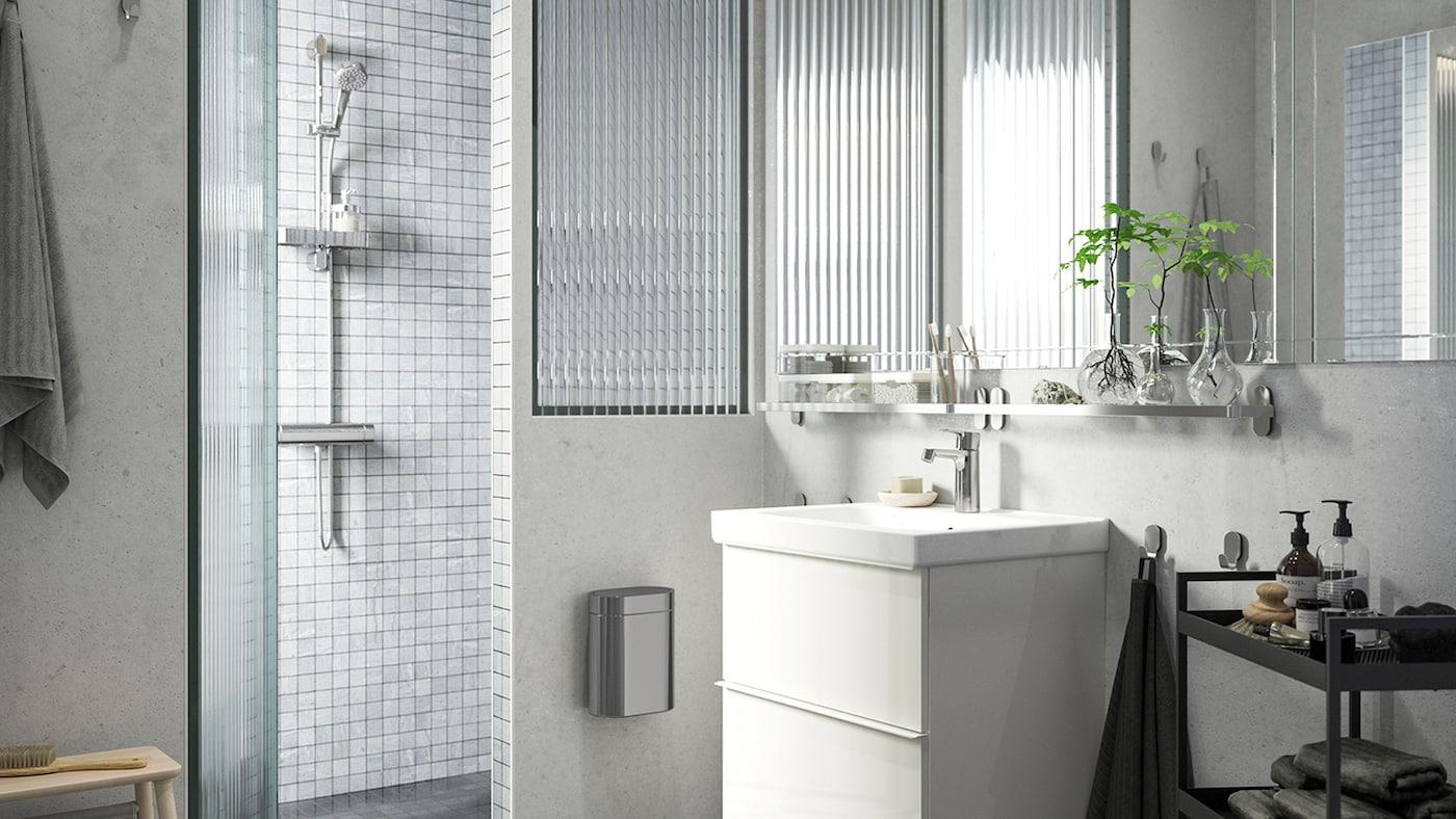 Ein hell erleuchtetes Badezimmer mit einem GODMORGON Waschbeckenschrank, einer Dusche mit grauen Kacheln und einem BROGRUND Duschset.