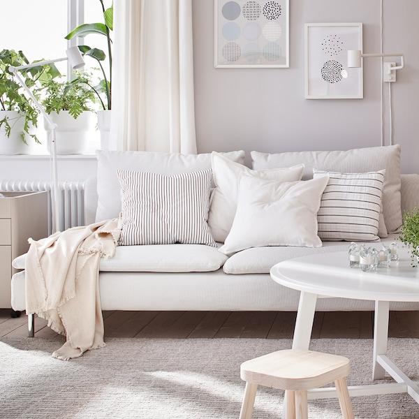 Ein hellbeiges Sofa in einem hellen Wohnzimmer, mit beigen und gestreiften Zierkissen.