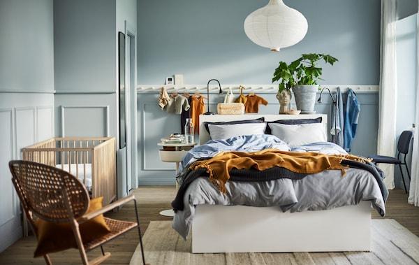 Ein hellblau gehaltenes Schlafzimmer mit einem weissen Bettgestell, einer weissen Leuchte, einer Hakenleiste, einem Rattanschaukelstuhl und einem SNIGLAR Babybett.