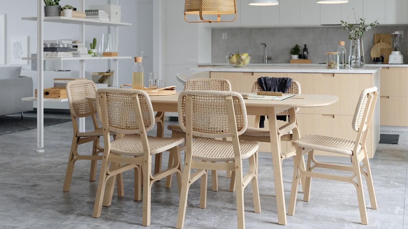 Ein heller Essplatz mit Tisch und Stühlen aus Bambus und Kraftpapier, einem weißen Raumteiler und einer Kücheninsel.