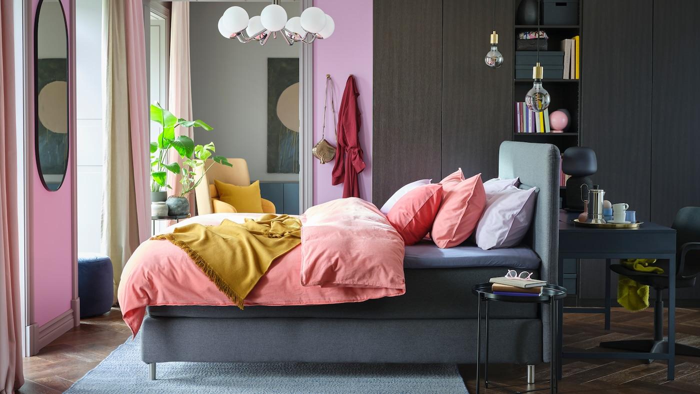 Ein helles Boxspringbett mit rosafarbener Bettwäsche und ein großer Kleiderschrank an einer Wand.