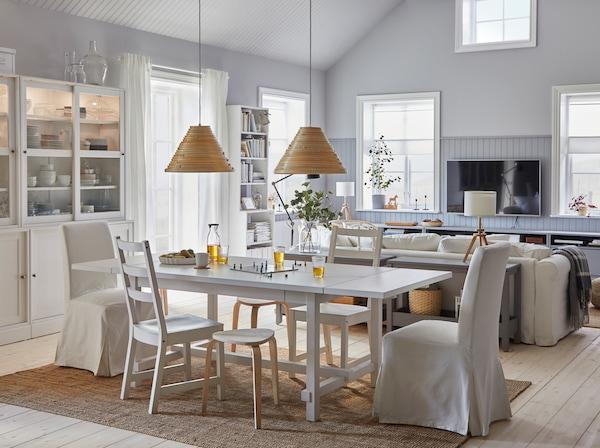 Ein helles Esszimmer mit weißem Ausziehtisch, weißem Regal, Sofa, Ablagetisch, Stuhl und Hängeleuchtenschirm.