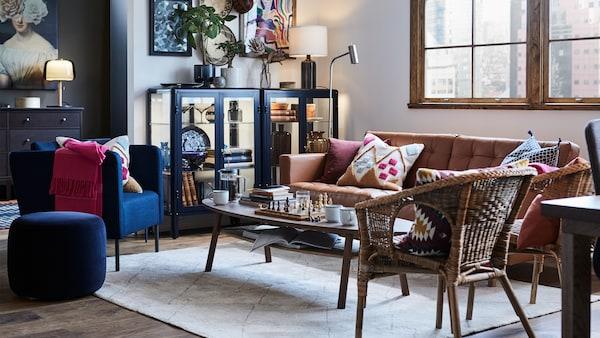 Ein helles, freundliches Wohnzimmer mit einem braunen Sofa, Rattansesseln und einem Couchtisch, auf dem Becher und ein Glas stehen.