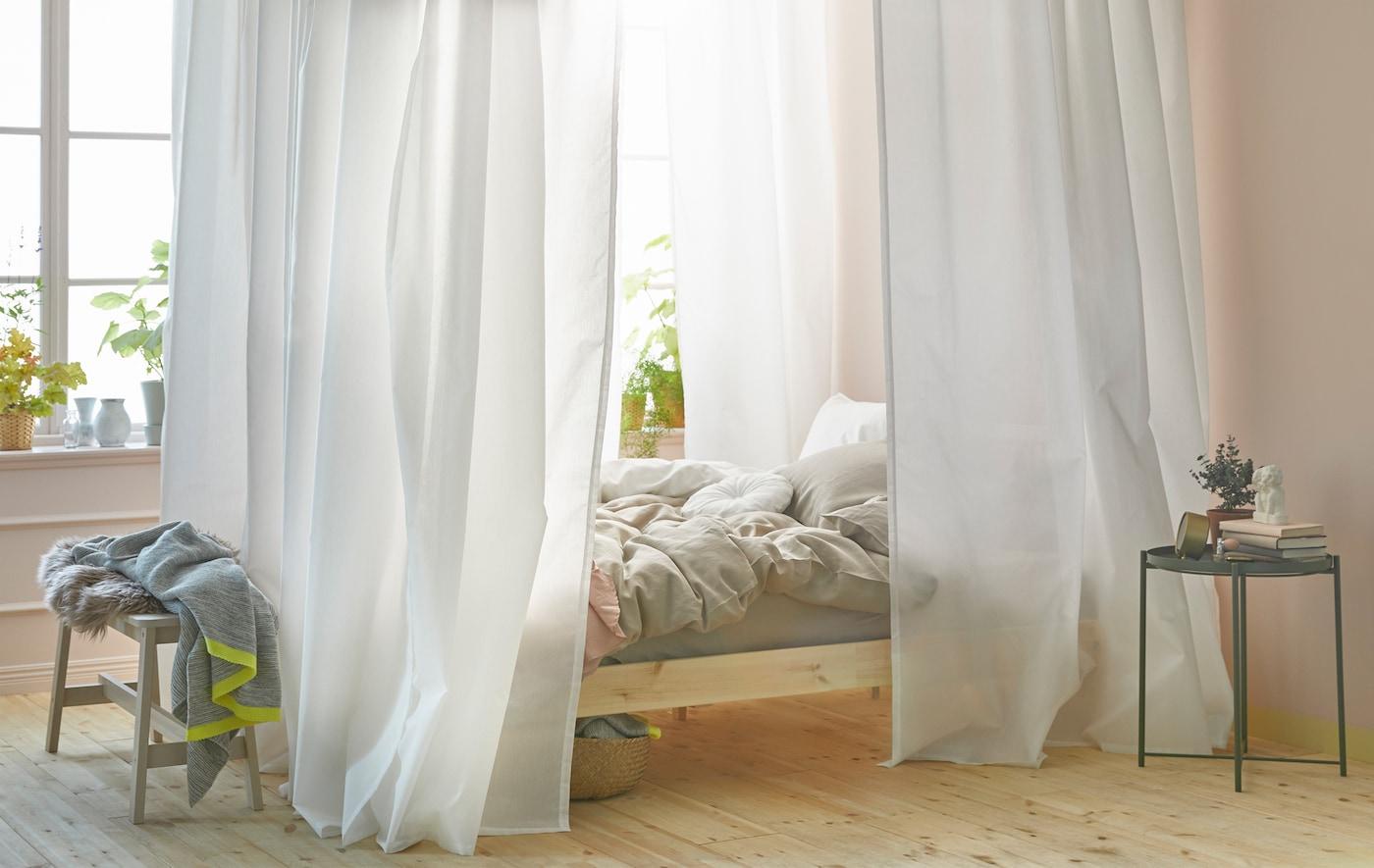 ein helles Schlafzimmer mit einem Bett. Rund ums Bett sind weiße Gardinen an der Decke befestigt.