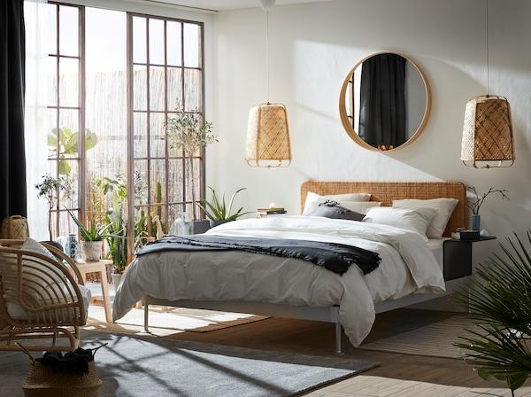 Ein helles Schlafzimmer mit vielen Naturmaterialien wie Rattan und Bambus. Neben dem DELAKTIG Bettgestell sind grosse Glastüren und ein Aussenbereich zu sehen.