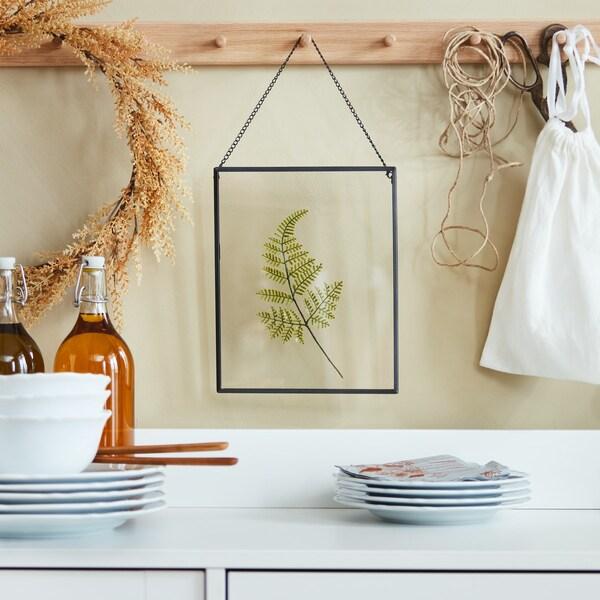 Ein HÖSTKVÄLL Bilderrahmen hängt an einer Holzleiste an der Wand.