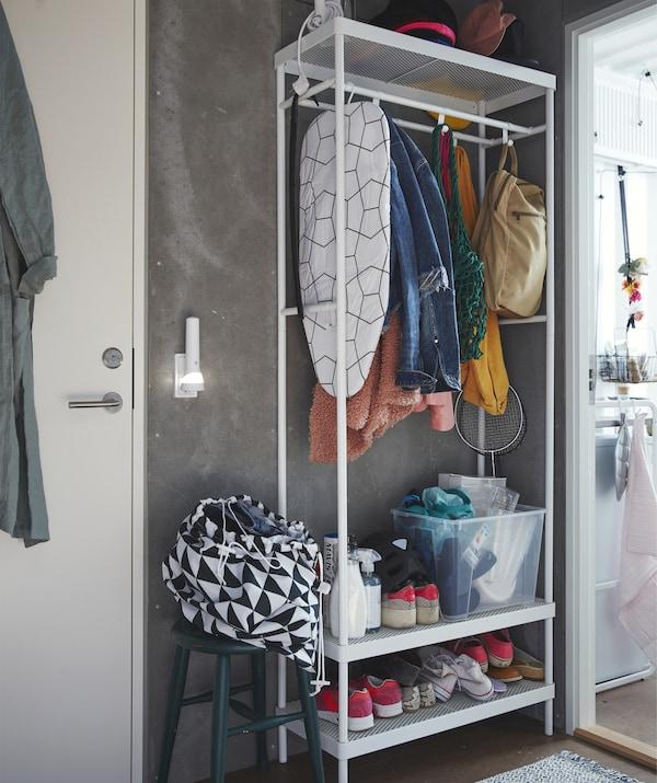 Ein hoher offener MACKAPÄR Garderobenständer mit Schuhablage mit Schuhen, Jacken und einem Bügelbrett auf Böden und an Stangen neben einer Tür