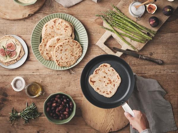 Ein Holztisch mit KNÅDA Fladenbrot auf einem grünen Teller und in einer Bratpfanne. Im Umfeld sind Gewürze, Spargel und Oliven zu sehen.