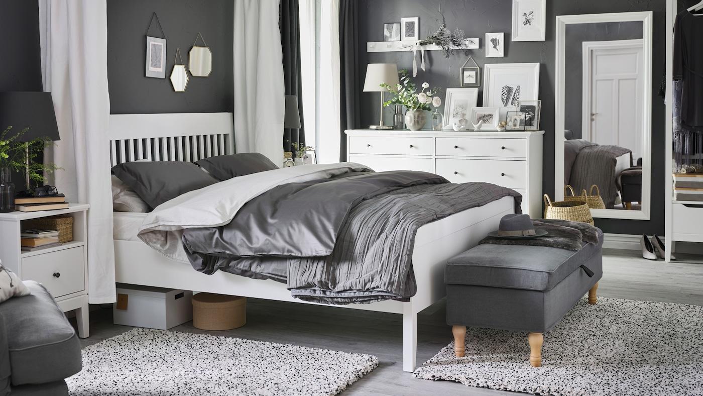 Ein IDANÄS Bettgestell, ein Ablagetisch und zwei Kommoden in Weiß stehen in einem Schlafzimmer; auf dem Bett liegt Bettzeug in LUKTJASMIN Bettwäsche-Set in Dunkelgrau.