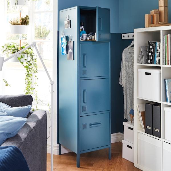 Ein IDÅSEN Hochschrank mit Schublade und Türen in Blau steht neben einem Fenster in einer Ecke.