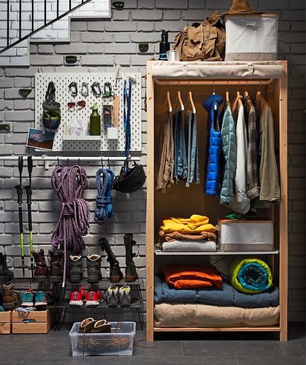 Ein IKEA IVAR Regal aus massiver Kiefer mit hochgerolltem Bezug. Darin sind Kleider auf Bügeln und Decken zu sehen.