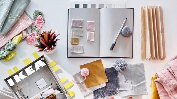 Ein IKEA Katalog mit Markierungen, ein offenes Notizbuch mit Stoffmustern und ein paar Stifte.