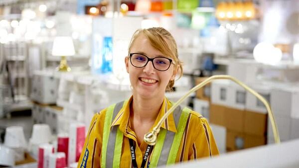 Ein IKEA Lehrling zur Einzelhandelskauffrau steht in der Lampenabteilung und lächelt