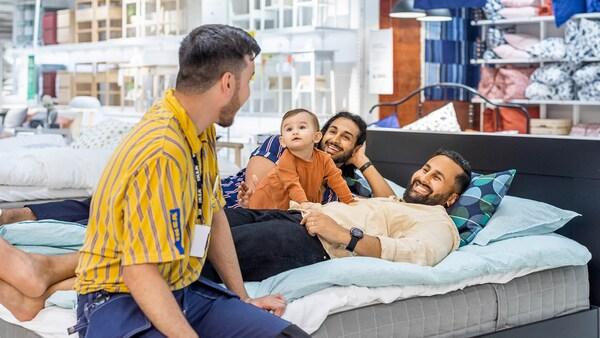 Ein IKEA Mitarbeiter berät ein homosexuelles Paar mit Kind beim Kauf einer neuen Matratze