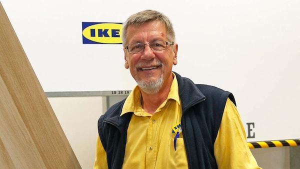 Ein IKEA Mitarbeiter hält ein Brett in der Hand und lacht