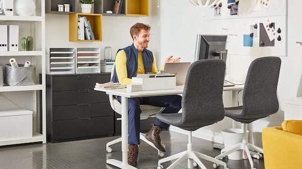 Ein IKEA Mitarbeiter sitzt an einen Schreibtisch während einer Online-Beratung mit einem Kunden