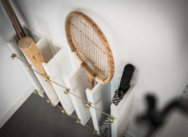 Ein IKEA MOSSLANDA Hack, bei dem MOSSLANDA Bilderleisten in Weiß senkrecht an der Wand befestigt wurden, um Platz für Tennis-, Hockey- und Baseballschläger, aber auch für Regenschirme zu schaffen.