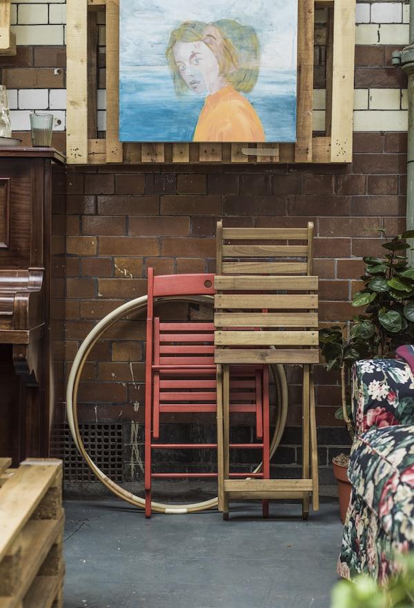 Ein IKEA TERJE Klappstuhl in Rot und ein faltbarer ASKHOLMEN Stuhl für draussen lehnen an einer gefliesten Wand.