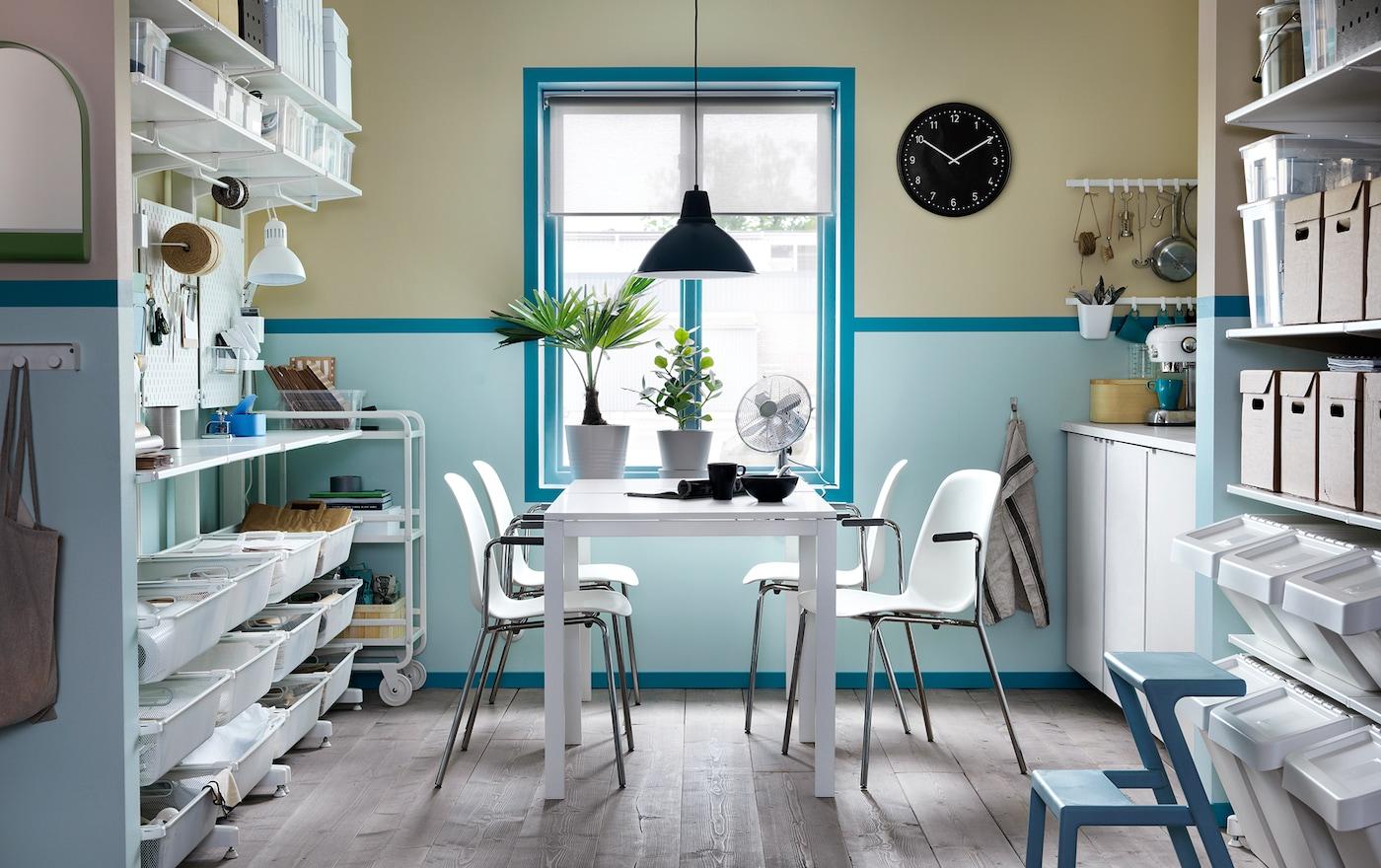 Ein in Blau & Weiß gehaltener Pausen- & Lagerraum mit weißem MELLTORP Tisch & LEIFARNE Stühlen