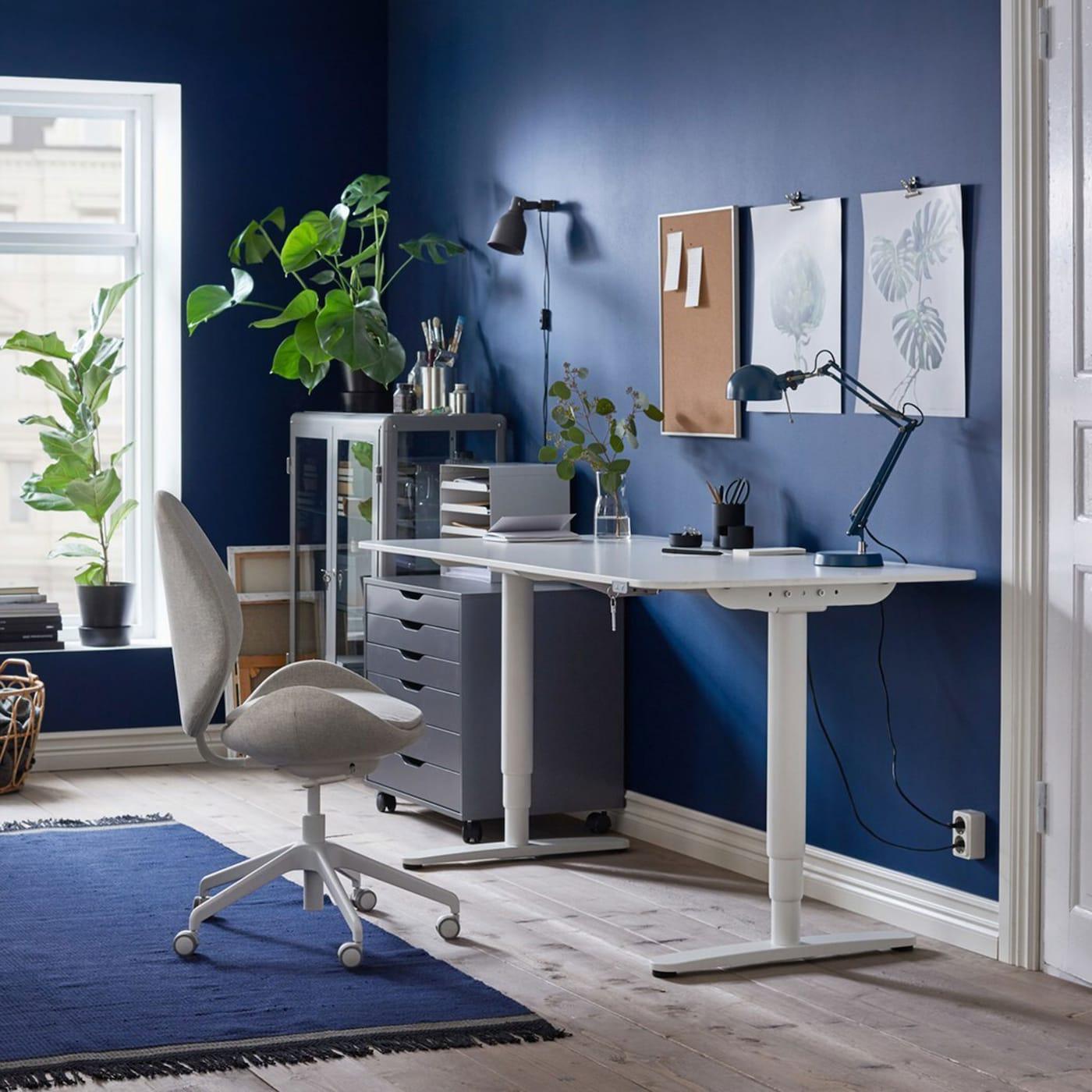 """Ein in Blau und Weiss gehaltener Heimarbeitsplatz mit dem ergonomischen HATTEFJÄLL Drehstuhl mit Bezug """"Gunnared"""" in Beige und BEKANT Sitz- und Stehschreibtisch in Weiss"""