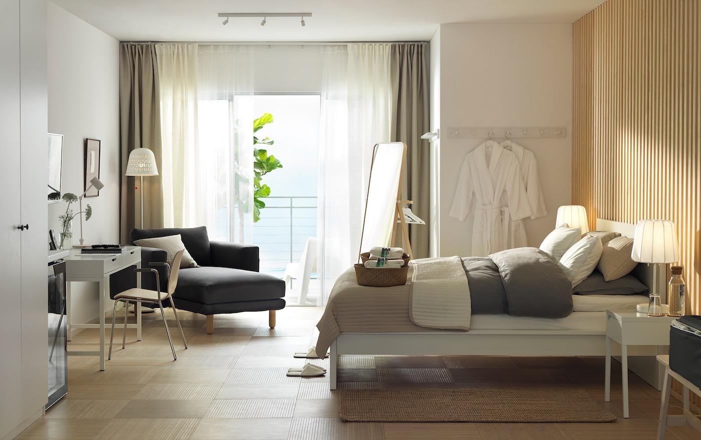 Ein in weiß gehaltenes Hotelzimmer zum Erholen & Entspannen mit Holzwand, MALM Bett & Récamiere