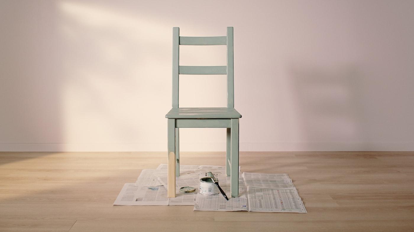 Ein IVAR Kiefer Stuhl, bis auf ein halbes Bein in grün gestrichen, steht gemeinsam mit einer Farbdose und Pinsel auf Zeitungspapier.