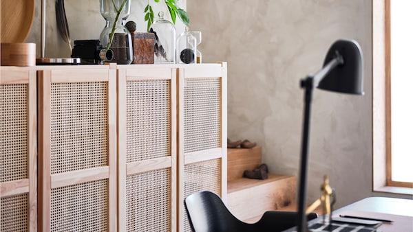 Ein IVAR Schrank mit Rattantüren zur Aufbewahrung. Obenauf sind persönliche Gegenstände zu sehen, davor steht ein Stuhl an einem Tisch.