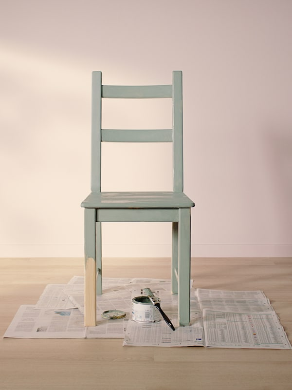 Ein IVAR Stuhl in Hellgrün steht auf alten Zeitungen in einem leeren Raum mit hellem Holzfußboden.