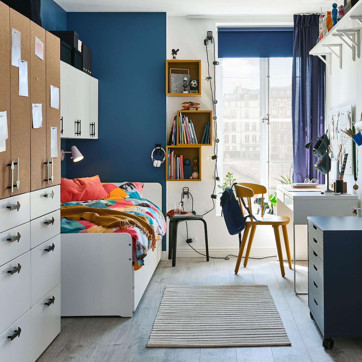 Ein Jugendzimmer mit einem weißen Bett, einem Kleiderschrank mit Türen mit Kork, an die Wand montierten Regalelementen in Goldbraun und einer blauen Gardine