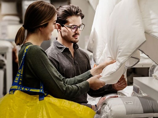 Ein junger Mann in schwarzer Kleidung geht durch ein IKEA Einrichtungshaus und trägt eine gelbe IKEA Einkaufstasche.