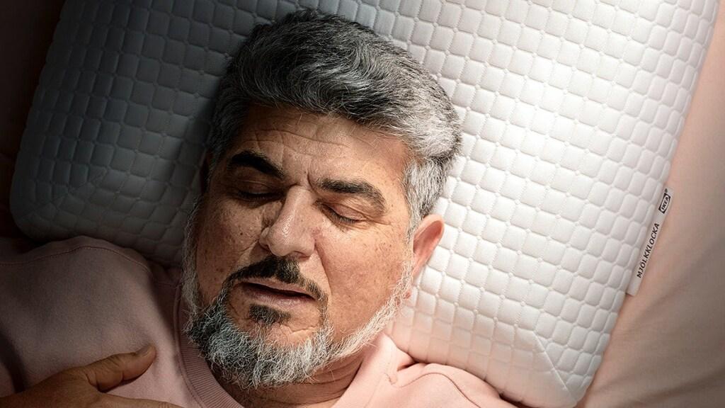 Ein junger Mann schläft tief und fest auf der Seite liegend auf einem ergonomischen PRAKTVÄDD Kissen für Seitenschläfer.
