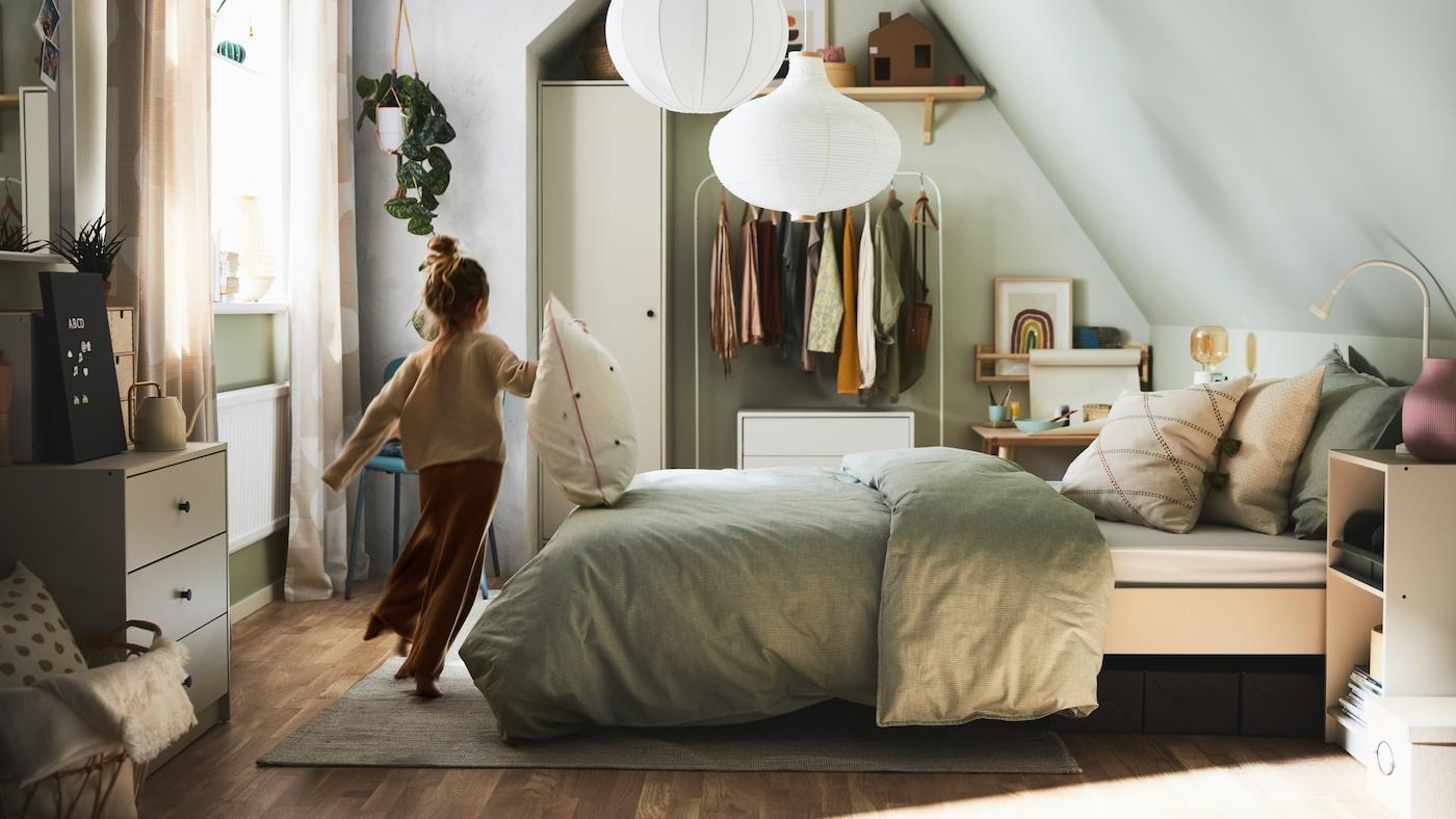 Ein Kind läuft in einem Schlafzimmer, das auch eine Kinderecke beinhaltet.
