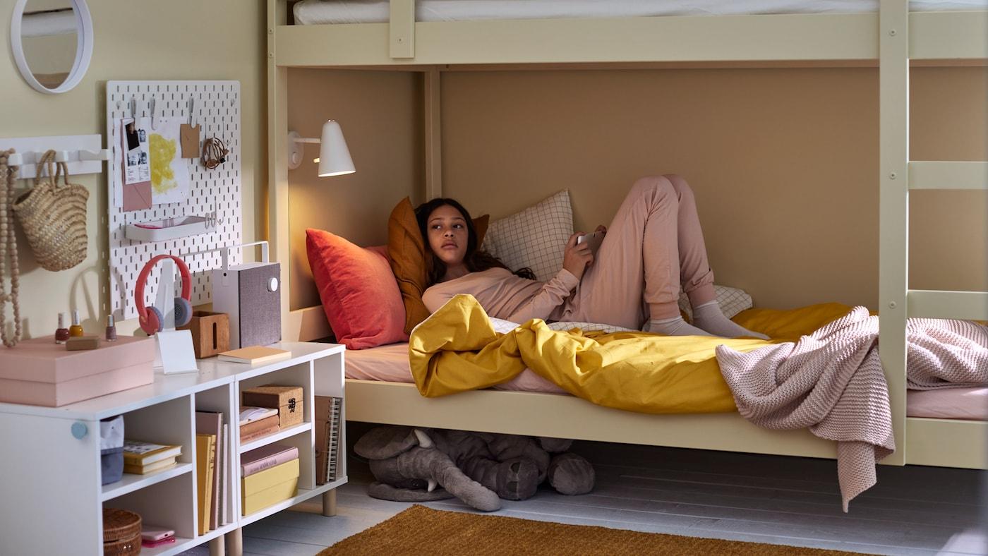 Ein Kind liegt im unteren Teil eines Etagenbetts mit Bettwäsche in verschiedenen Farben.