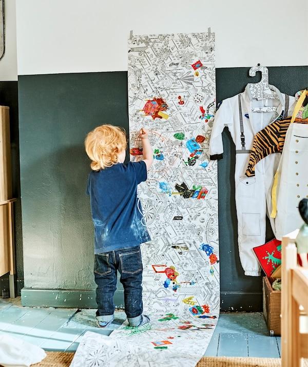 Ein Kind malt eine LUSTIGT Malpapierrolle aus, die an der Wand hängt, hier u. a. mit einem VÄNSKAPLIG Kinderkleiderbügel
