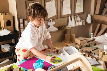 Ein Kind malt etwas an einem Tisch