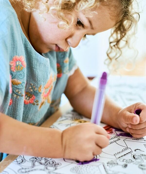 Ein Kind malt mit einem Stift eine Zeichnung auf LUSTIGT Malpapierrolle aus.
